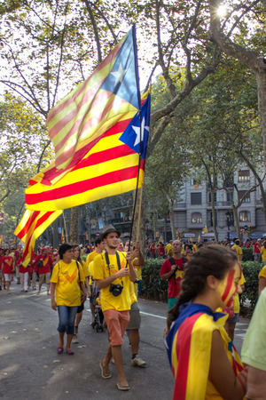 strret: BARCELONA, SPAIN - SEPT. 11: Teenagers with flag manifesting ingependence on the strret of Barcelona during the National Day of Catalonia on Sept. 11, 2014 in Barcelona, Spain.