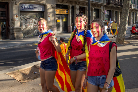BARCELONA, SPAIN - SEPT. 11: Teenagers on the background of people manifesting ingependence on the strret of Barcelona during the National Day of Catalonia on Sept. 11, 2014 in Barcelona, Spain