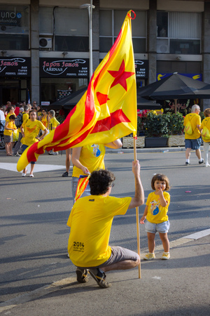 strret: BARCELONA, SPAIN - SEPT. 11: Family with flag manifesting ingependence on the strret of Barcelona during the National Day of Catalonia on Sept. 11, 2014 in Barcelona, Spain.