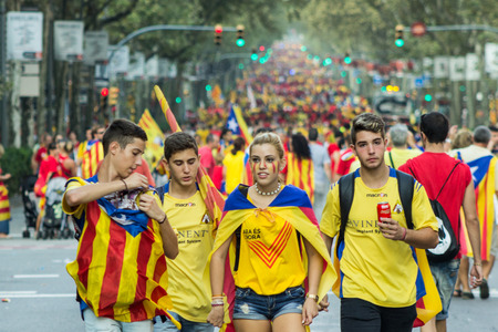 strret: BARCELONA, SPAIN - SEPT. 11: Teenagers on the background of people manifasteting ingependence on the strret of Barcelona during the National Day of Catalonia on Sept. 11, 2014 in Barcelona, Spain.