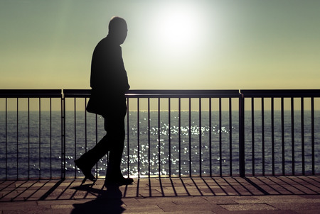 A dark silhouette of an unrecognizable man walking along a beach promenade in summer sunrise photo