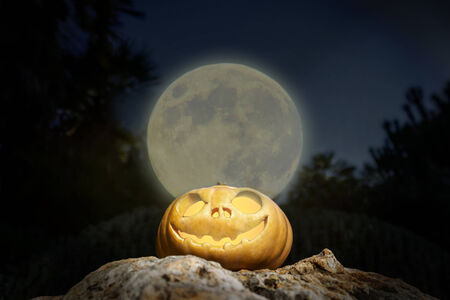 rock bottom: Spooky Halloween scary pumpkin jack-o-lantern with a smile in moon light on a rock from bottom perspective template illustration
