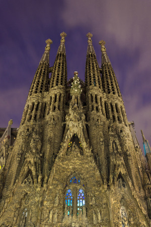 familia: BARCELONA, SPAIN - NOVEMBER 22: La Sagrada Familia - cathedral designed by Antonio Gaudi, Night view from oldest facade from bottom, 2014 Barcelona Stock Photo