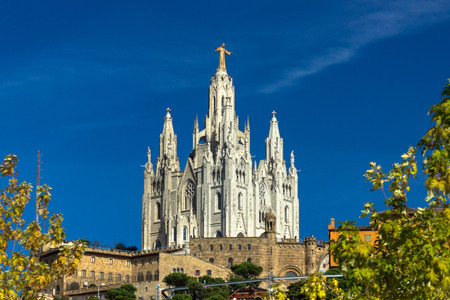 sacred heart: Tibidabo church under the trees - temple at the top of mountai in Barcelona, Spain Stock Photo