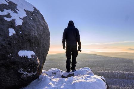 sudetes: Silhouette of photographer standing on the  snowy mountains in rays of sunrise. Sudetes, Poland, Europe. Amazing world. Stock Photo