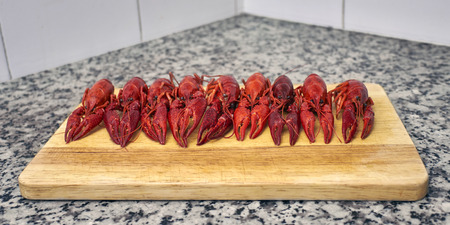 fluvial: Nine red river crayfish on cutting board on grey granite worktop in front perspective Stock Photo