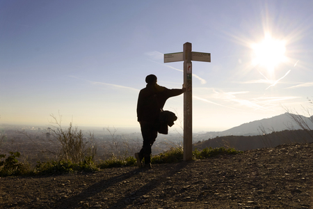 lean over: Silhouette of a man lean on the signpost in rays of sun over the city of Barcelona. Spain, Europe. Amazing World. Stock Photo