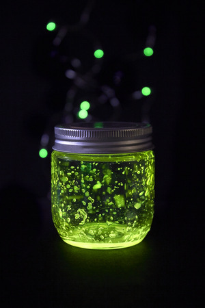 Closed green light glowing jar in the dark  background witch sparkling bokeh Фото со стока