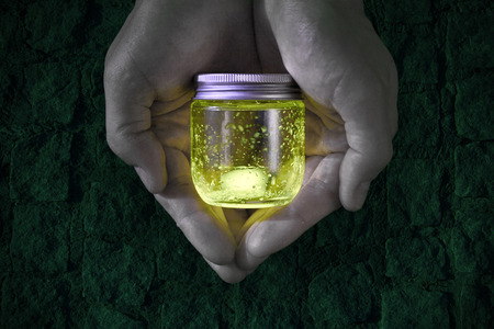 Magical green light glowing jar in the hands