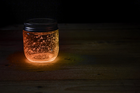firefly: Closed orange light glowing jar on the wood boards in the darkness Stock Photo