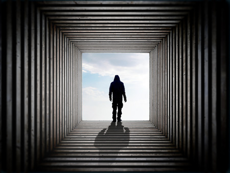 Silhouette of a man on the edge of the wood tunnel looking down.