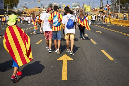 BARCELONA, SPAIN - 11 SEPTEMBER 2015: People waering Catalan flag at the day of Catalonia. Like a Hero in good direction.