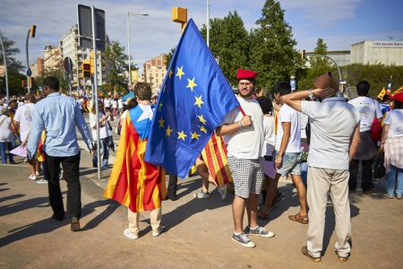 happieness: BARCELONA, SPAIN - 11 SEPTEMBER 2015: Crowd of people at the day of Catalonia, in front guy in traditional hat with EU flag.