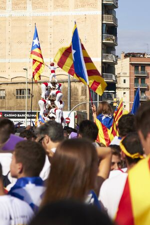 BARCELONA, SPAIN - 11 SEPTEMBER 2015: White Castelliers traditional tower at the day of Catalonia, behind the flags