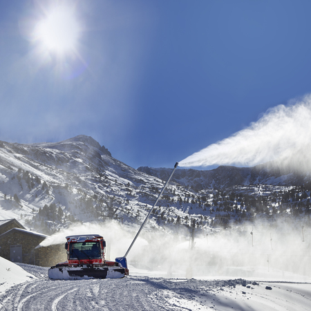 snow grooming machine: Preparation of ski resort in Pyrenees by red ratrack vehicle and snow canon Stock Photo