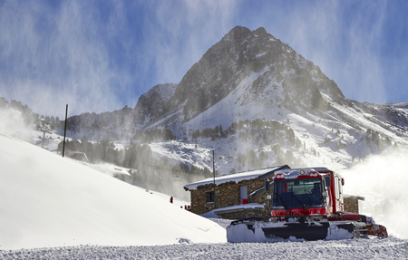 snow grooming machine: Red ratrack vehicle for snow preparation at ski resort in Andorra, Pyrenees, Europe