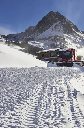 snow grooming machine: Red ratrack vehicle for snow preparation at ski resort in Andorra, Pyrenees mountain, Europe Stock Photo