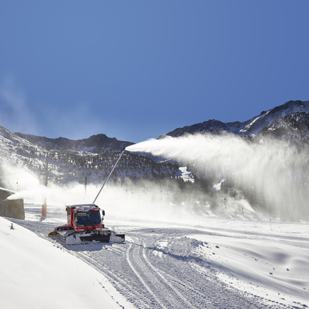 snow grooming machine: Preparation of ski resort in Pyrenees by red ratrack vehicle and snow canon, Andorra, Europe