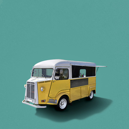 Yellow retro fast food truck on turquoise background, template with copy space