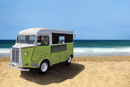 sea food: Green retro fast food truck on the beach, vertical template with copy space Stock Photo