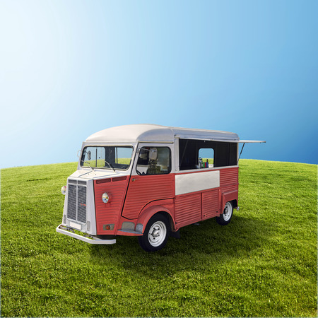 Red retro fast food truck on green field with blue sky, template with copy space