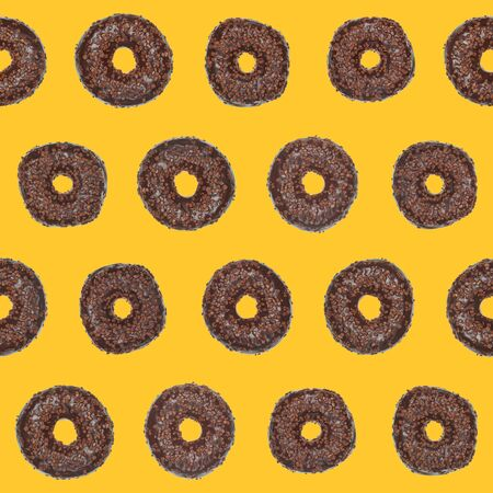 cake topping: Sameless pattern of chocolate donuts on yellow background