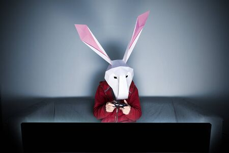 Rabbit geometric mask gamer on the sofa in front of tv