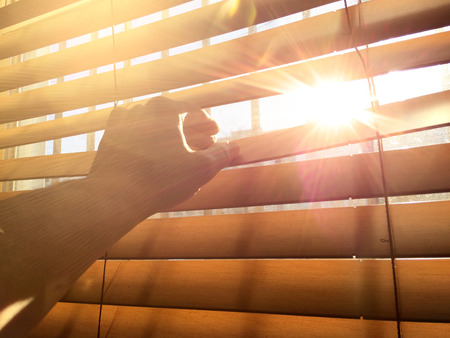 succes: Hand showing warm midday sun behind window blind.