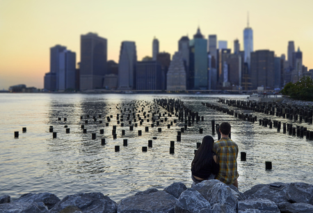 Lovers at sunset behind Manhattan in front of palisade pier on East river Banque d'images