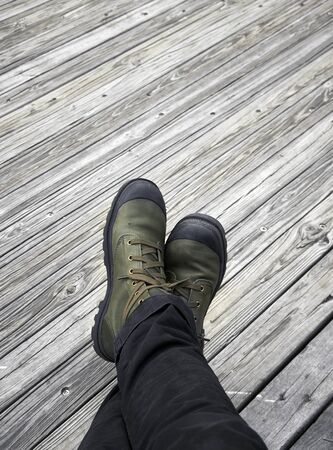 walk path: Legs in leather shoes on wood walk path background.