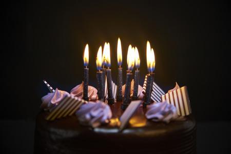 Chockolate birthday cake with candles on black background closeup