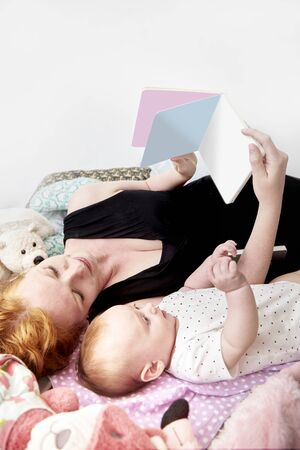 Mother reading book to her doughter baby sorrounded with toys on bed.