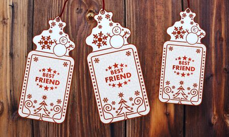seasonal 3d rendered christmas labels with best friend sticker in front of a nice wooden background photo