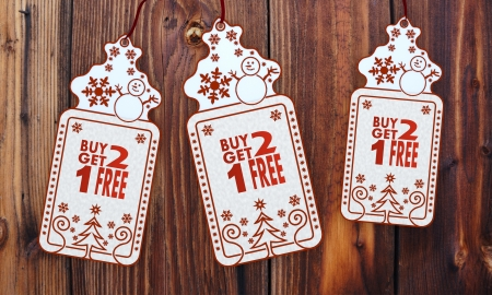 friendly 3d rendered christmas labels with buy two get one free sticker in front of a nice wooden background photo