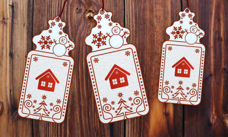 cute 3d rendered christmas labels with house sign in front of a nice wooden background photo