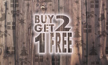 get one: organic wooden buy two get one free symbol on wood with burned in christmas symbols such as snowflakes presents and stars Stock Photo