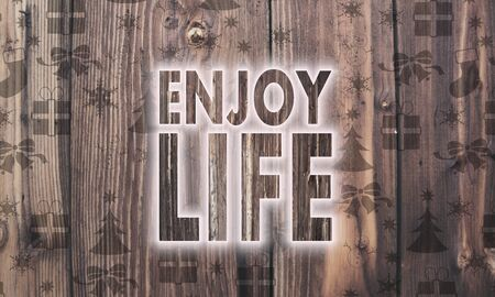 enjoy life: seasonal wooden enjoy life symbol on wood with burned in christmas symbols such as snowflakes presents and stars Stock Photo