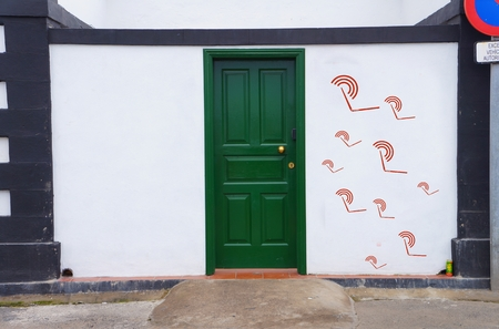 concept image of a dirty green door with red netbook symbol on the right wall next to it photo