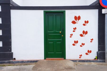 autumnn: concept image of a nostalgia green door with red oak leaves symbol on the right wall next to it