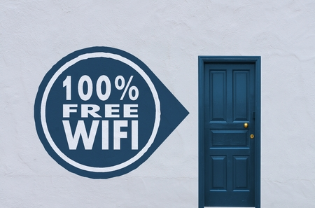 concept image of a wooden blue entry door in a white wall with a 100 percent free wifi symbol on the left side photo