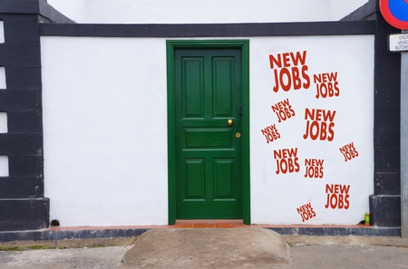 concept image of a closed green door with red new jobs symbol on the right wall next to it photo