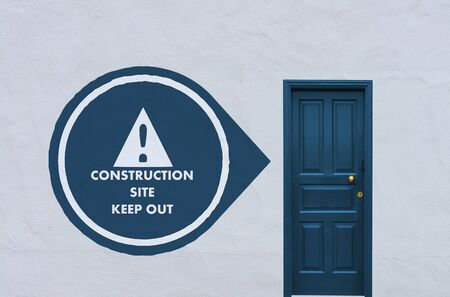 concept image of a wooden blue entry door in a white wall with a construction site icon on the left side Stock Photo - 27621991