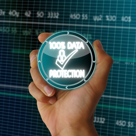 a hand presents digital round button with a data protection sign on it in front of a electronic data table from stock market