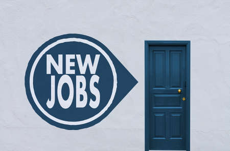 new entry: concept image of a closed blue entry door in a white wall with a new jobs sign on the left side Stock Photo