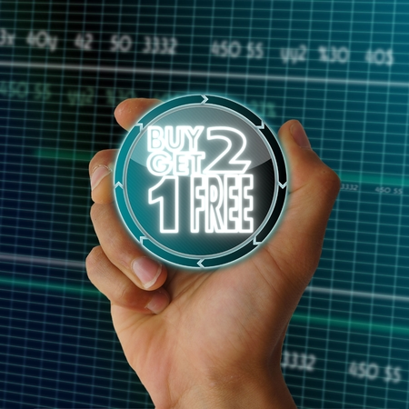 get one: a hand presents conceptual round button with a buy two get one free symbol on it in front of a electronic data table from stock market