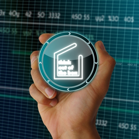a hand presents future round button with a think out of the box symbol on it in front of a electronic data table from stock market photo