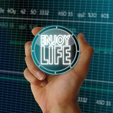 enjoy life: a hand presents future round button with a enjoy life symbol on it in front of a electronic data table from stock market Stock Photo