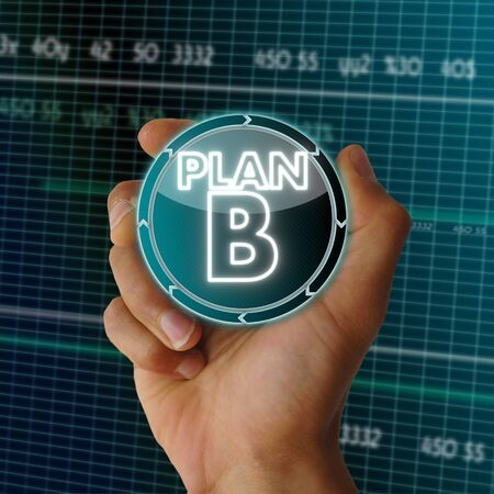 a hand presents digital round button with a plan b sign on it in front of a electronic data table from stock market photo