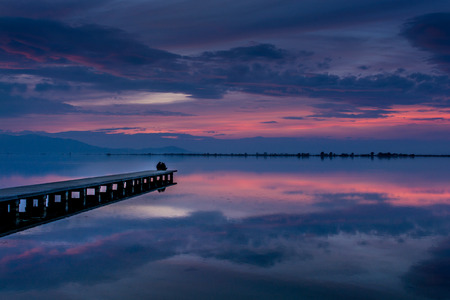 Calm blue waters over a dramatic sunset sky shortly before night time at Delta Ebre river, Spain Stock Photo