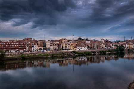 Dramatic view of the village Mora la Nova and the Ebre river at sunrise With cloudy sky